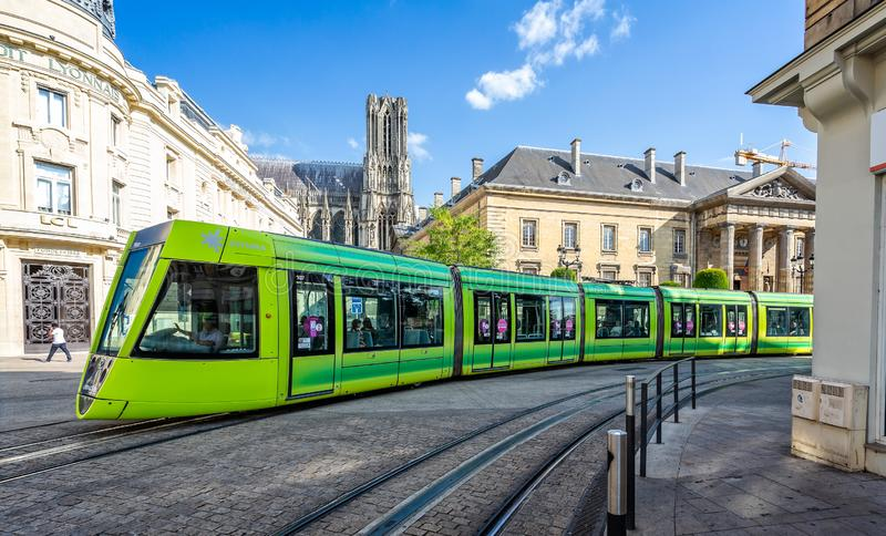 Flourescent green tram passing in front of Reims Cathedral stock photo