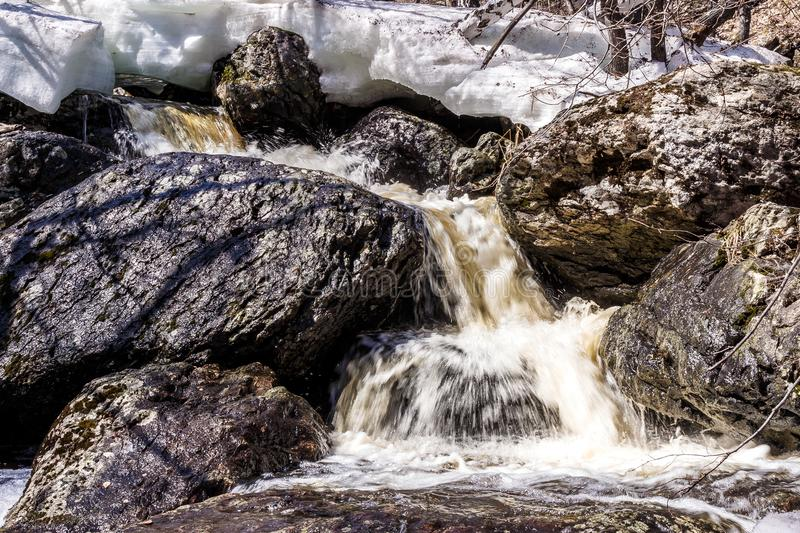 The flow of bubbling melt water in the mountains. In the spring stock image