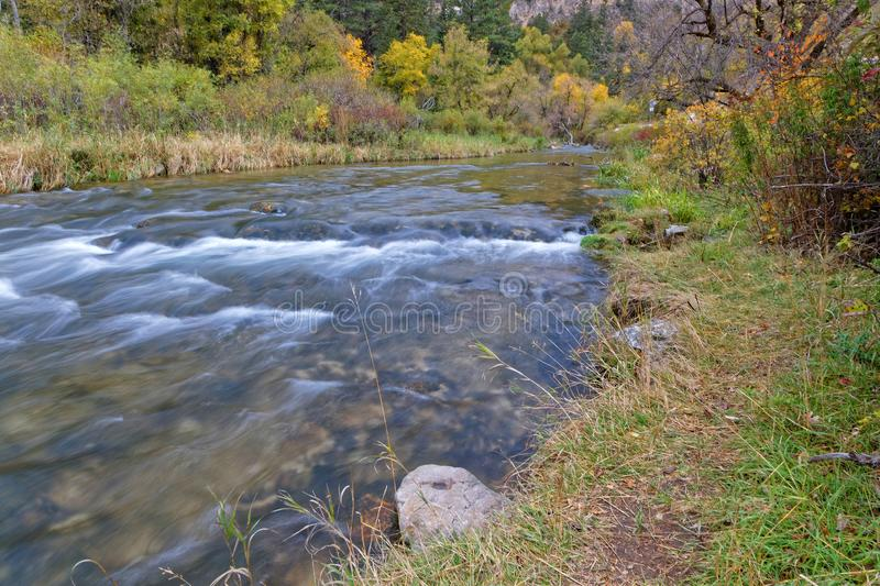 Flow of a river in Spearfish Canyon. Low speed on a river in a fall landscape in Spearfish Canyon, Black Hills, South Dakota royalty free stock images