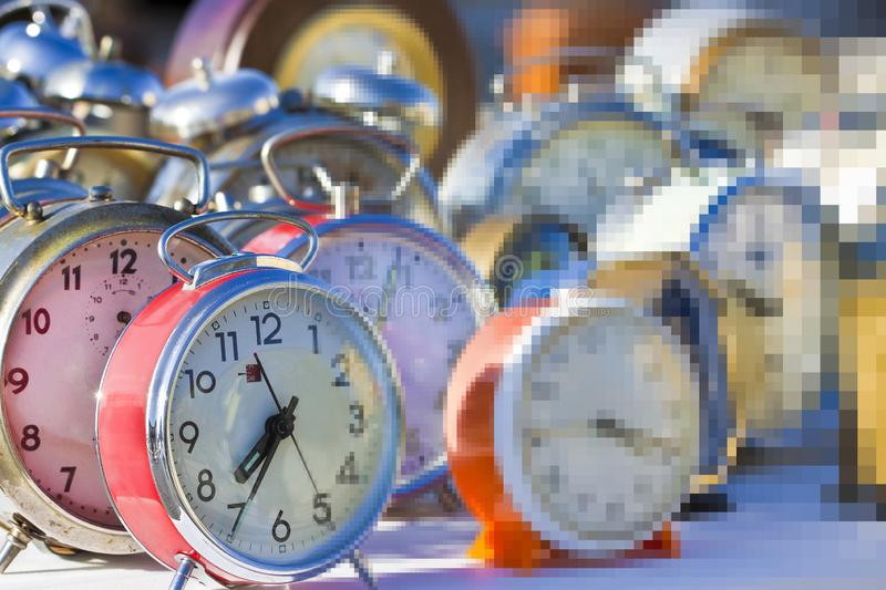 Flow of time is just an illusion - concept image with old colored metal table clocks.  royalty free stock image