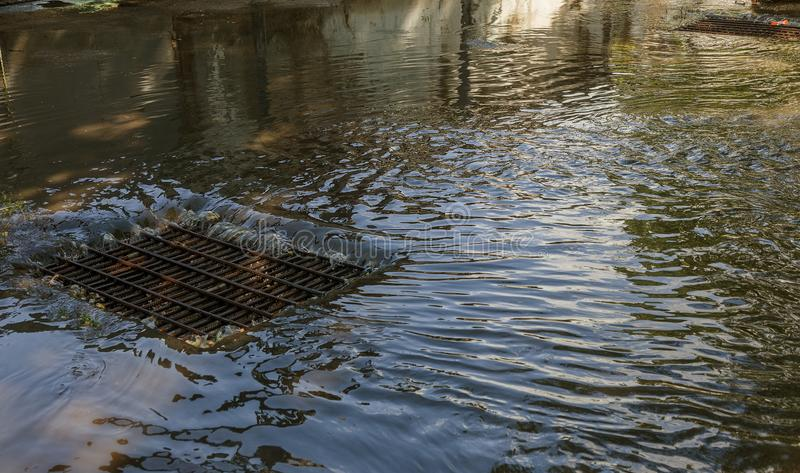 Flow of water during heavy rain and clogging of street sewage. The flow of water during a strong hurricane in storm sewers. Sewage. Storm system along the road royalty free stock image