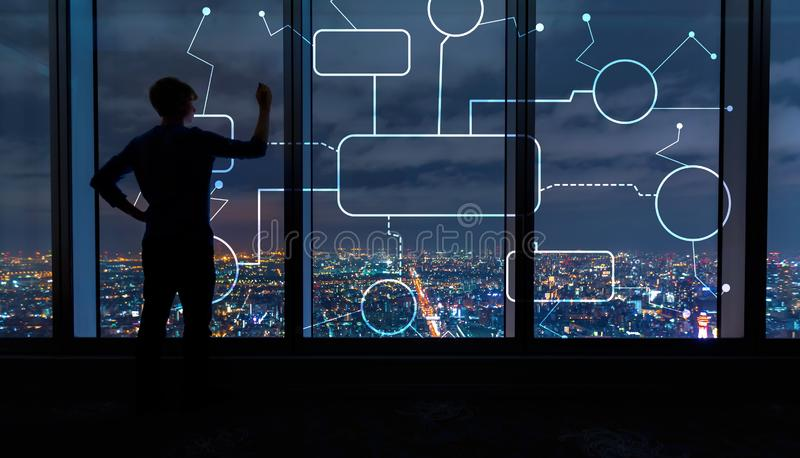 Flowchart with man by large windows at night. Flowchart with man writing on large windows high above a sprawling city at night royalty free stock photography