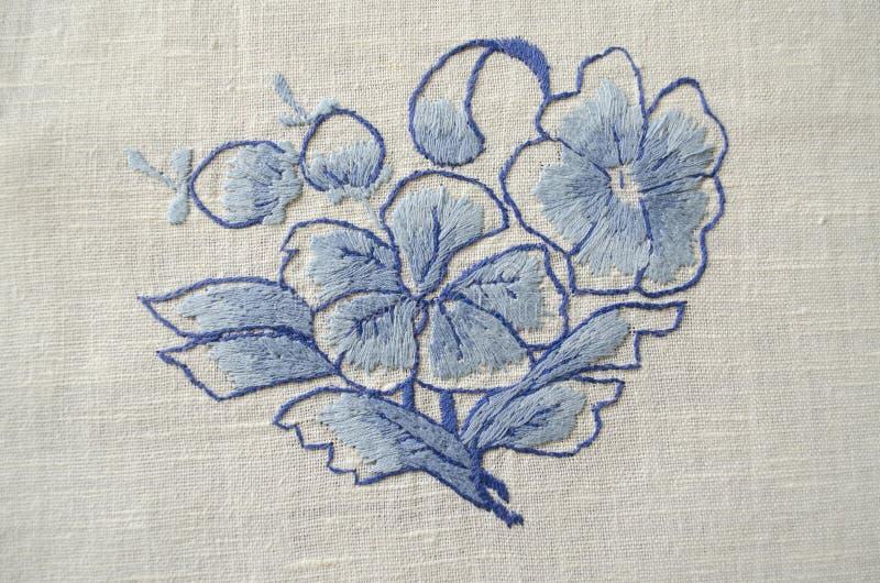 Flowerbleu brodé de point de satinsur le tissu de coton illustration de vecteur