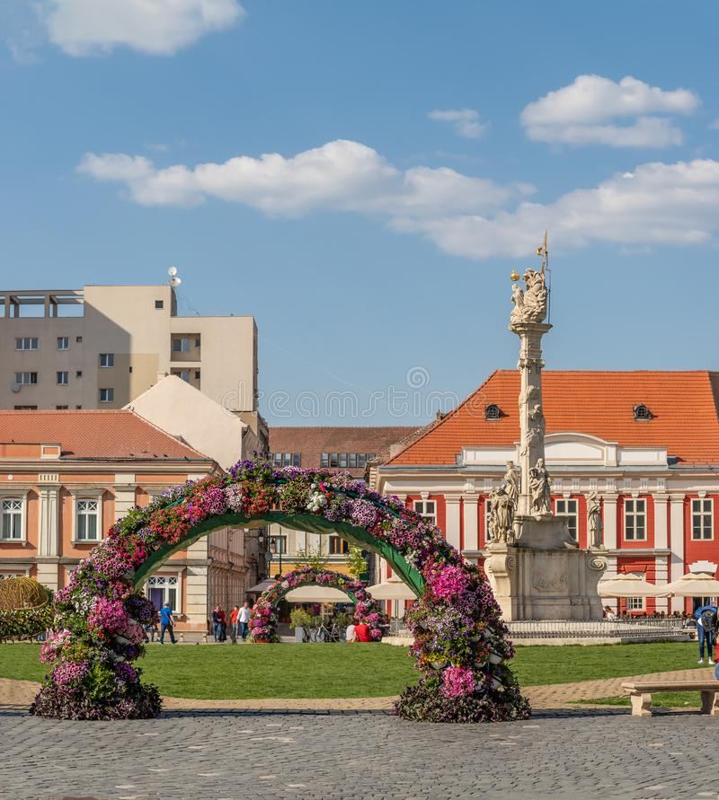 Flower Arc with Holy Trinity Statue in Background in Union Square in Timisoara. Romania royalty free stock images