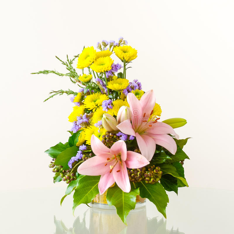 Flower arrangement. Artistic flower arrangement in a container on a glossy table stock photography