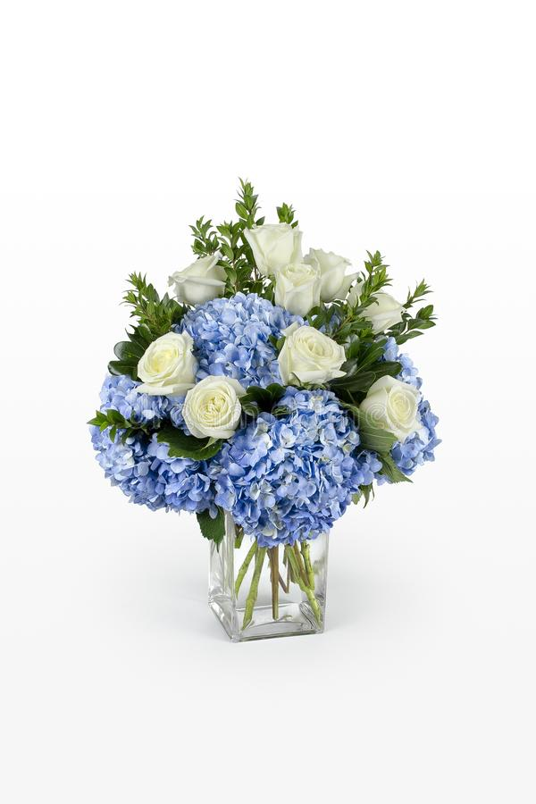Blue hydrangea and white roses flower arrangement in a large glass vase. Minimal floral design by a florist. royalty free stock photos