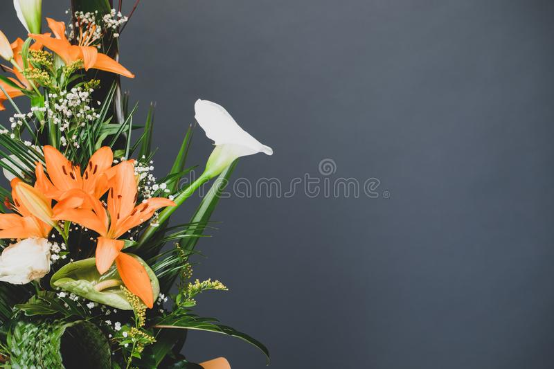 Flower arrangement bouquet to the side with grey studio background copy space. Floral concept background with gray negative space stock photo