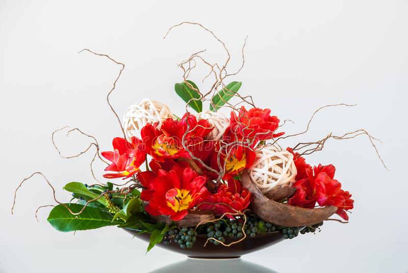 Flower arrangement. Ikebana-like artistic flower arrangement in a container on a glossy table royalty free stock photography