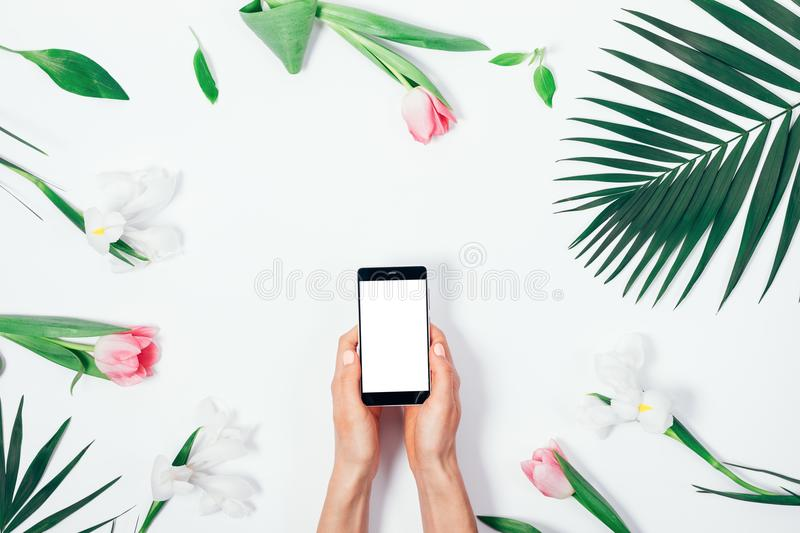 Flower arrangement and mobile phone with blank screen. In female hands on white table top view royalty free stock photo
