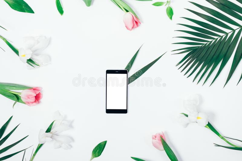 Flower arrangement and mobile phone. With blank screen on white table top view royalty free stock photography