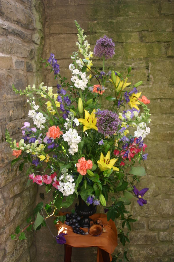 Flower arrangement. In outdoor alcove. Brick wall behind stock image
