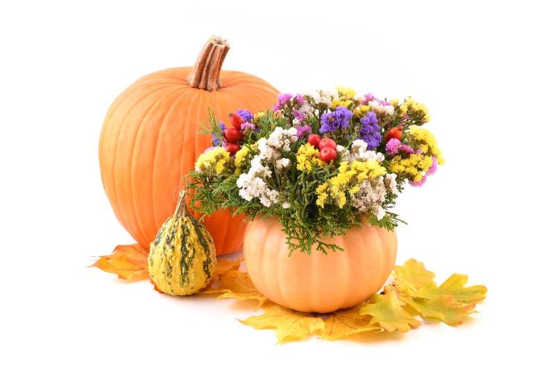 Flower arrangement with pumpkin vase. Fall flower arrangement with pumpkin vase over white royalty free stock images