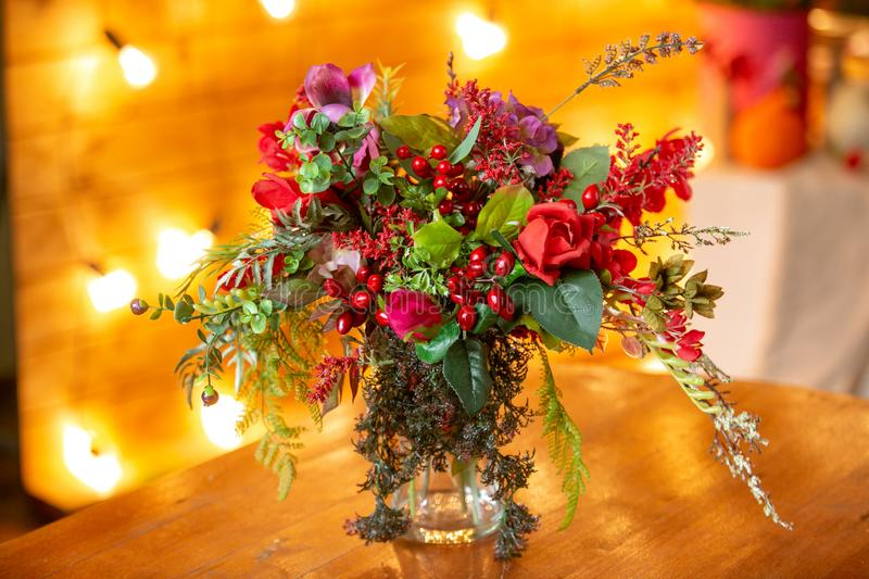 Flower arrangement with red berries, red roses and greens on the table. Flower arrangement with red berries, red roses and greens in a transparent vase on the royalty free stock photos