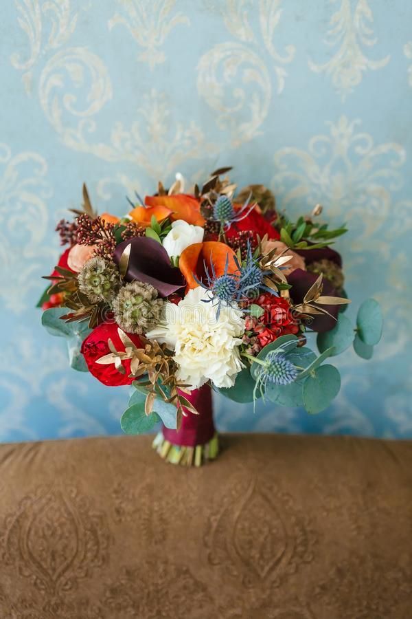 Flower arrangement for a wedding party. The bouquet of flowers on blue wall background. Wedding. Artwork. Flower arrangement for a wedding party. The bouquet of royalty free stock image