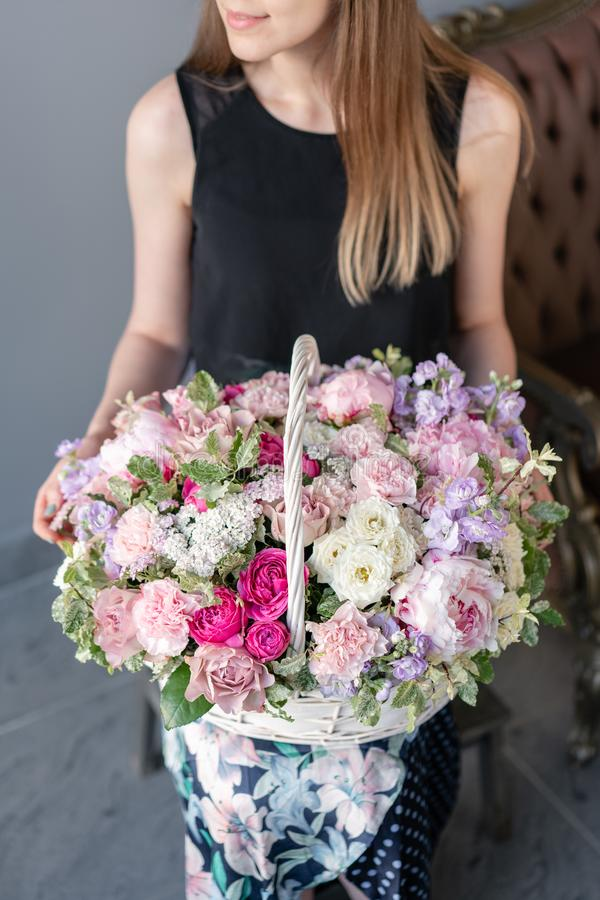 Flower arrangement in Wicker basket. Beautiful bouquet of mixed flowers in woman hand. Floral shop concept . Handsome royalty free stock images