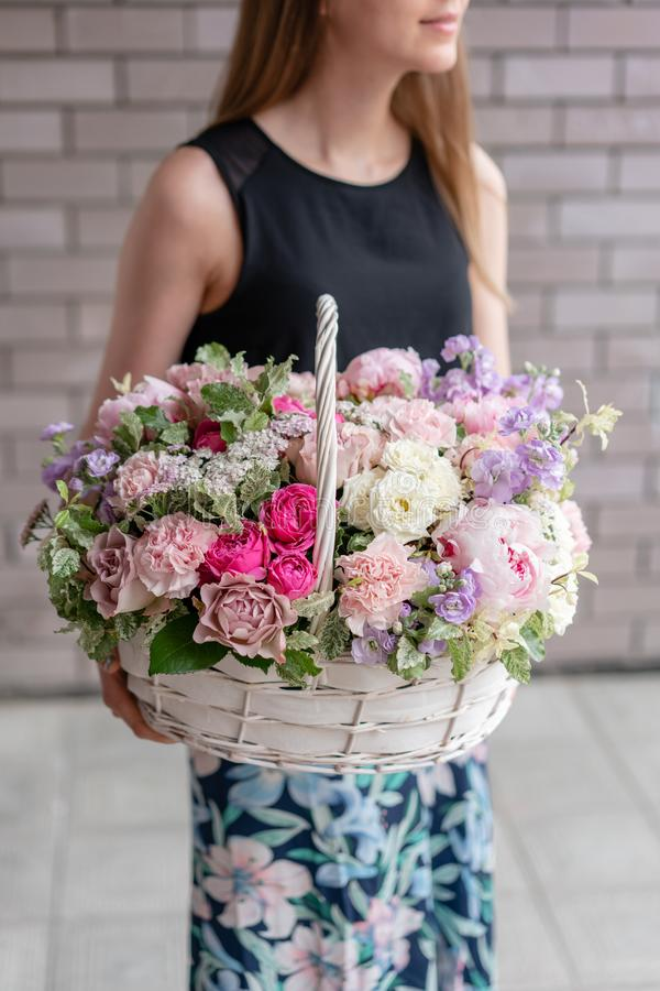 Flower arrangement in Wicker basket. Beautiful bouquet of mixed flowers in woman hand. Floral shop concept . Handsome royalty free stock photo