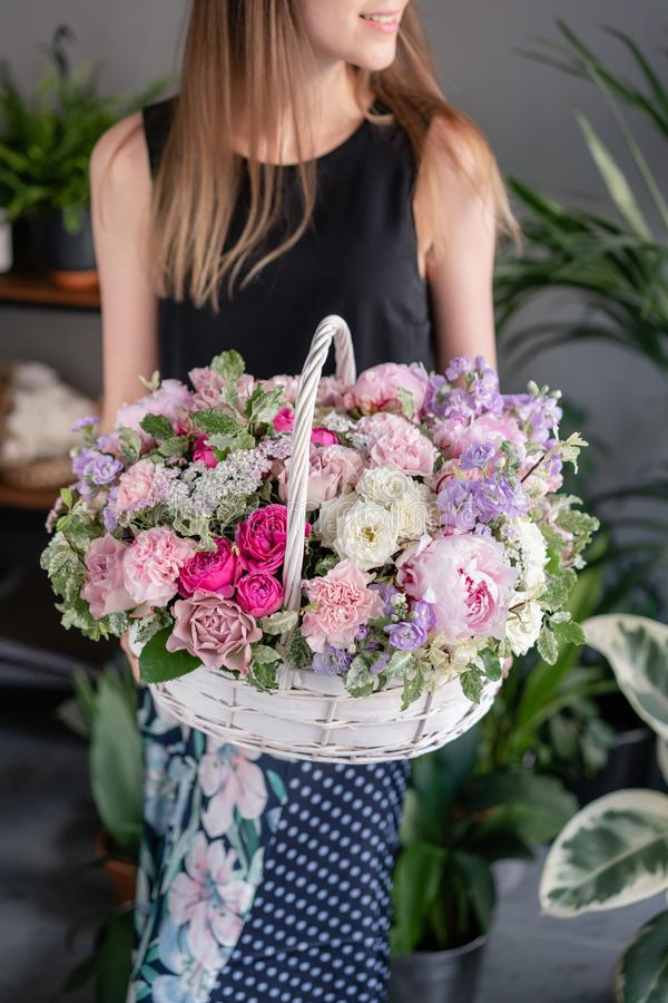 Flower arrangement in Wicker basket. Beautiful bouquet of mixed flowers in woman hand. Floral shop concept . Handsome stock photo