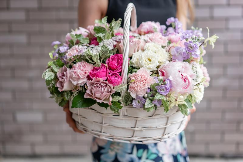 Flower arrangement in Wicker basket. Beautiful bouquet of mixed flowers in woman hand. Floral shop concept . Handsome stock photos