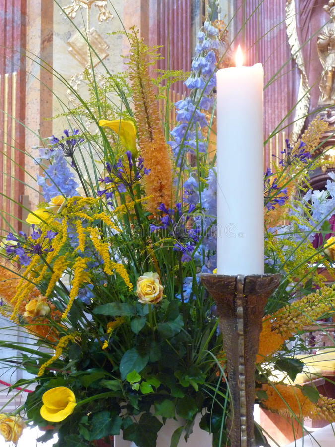 Flower arrangements. A lighted candle and a flower arrangement royalty free stock photo