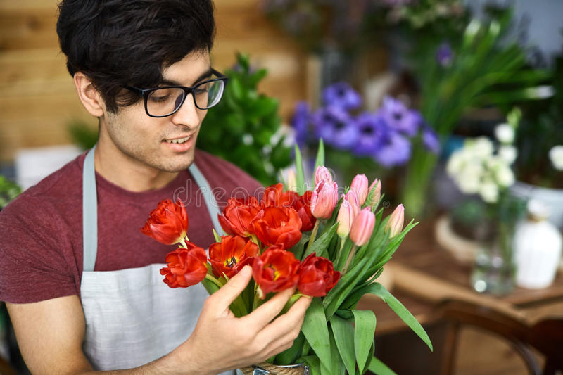 Flower arranging. Owner of flower-shop looking at fresh tulips royalty free stock images