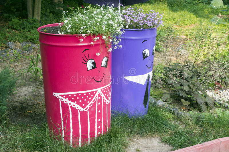 A flower bed in the barrels. A flower bed in colored glasses stock image