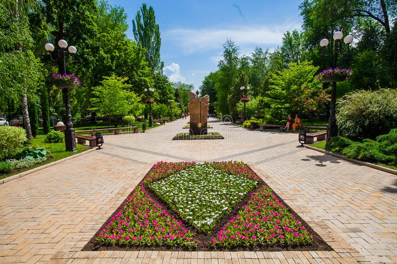 Flower bed and decorative statue in urban public place in Donetsk royalty free stock photography