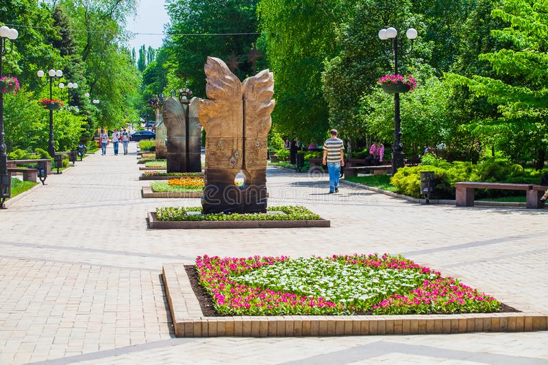 Flower bed and decorative statues in urban public place in Donetsk stock images