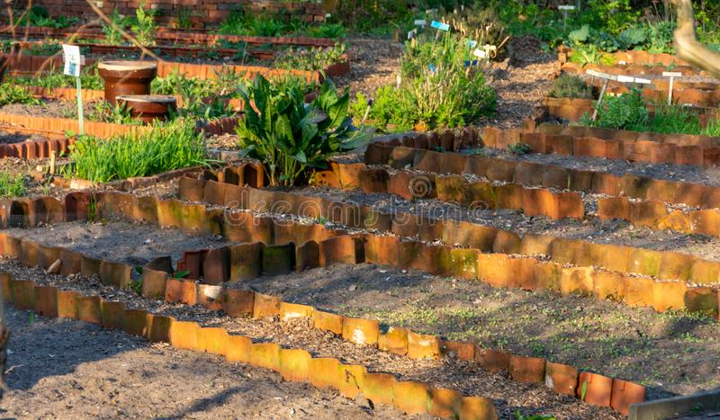 Flower beds bordered with roof tiles royalty free stock photography