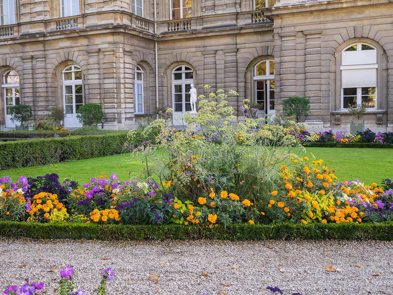 Flower beds and gravel walk in front of French Senate building,. Flower beds and gravel walk behind French Senate building in the Luxembourg Garden, Paris stock photo