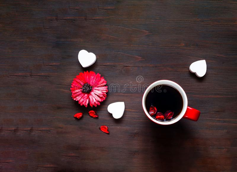 Flower and big red cup of coffee on wooden background. Festive concept stock photo