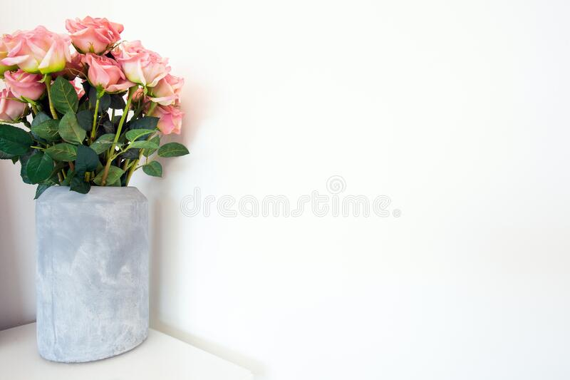 Flower bouquet of beautiful pink roses in concrete modern vase near white background, space for text royalty free stock image