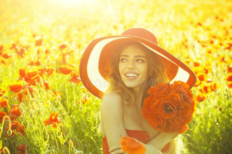 Flower bouquet at smiling girl in retro hat, poppy field. Flower bouquet at smiling girl with long curly hair in red dress and retro hat in field of poppy seed royalty free stock images