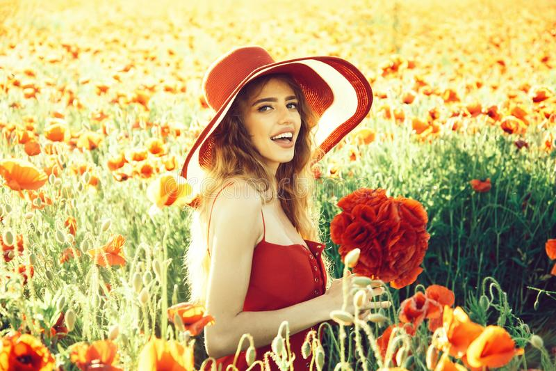 Flower bouquet at smiling girl in retro hat, poppy field. Flower bouquet at smiling girl with long curly hair in red dress and retro hat in field of poppy seed royalty free stock photography