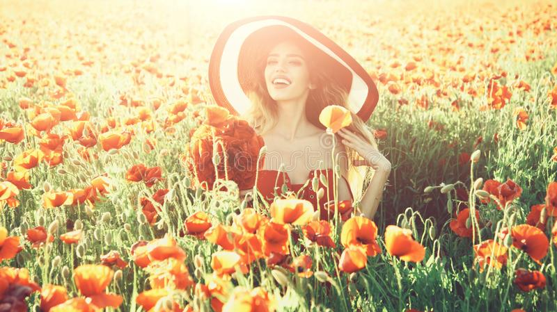 Flower bouquet at smiling girl in retro hat, poppy field. Flower bouquet at smiling girl with long curly hair in red dress and retro hat in field of poppy seed royalty free stock photos