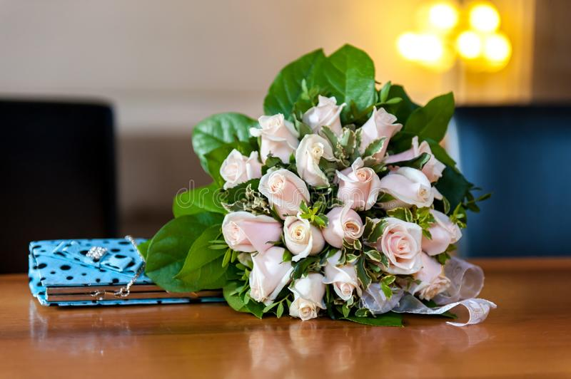 Flower bouquet and turquoise purse on wood table stock image