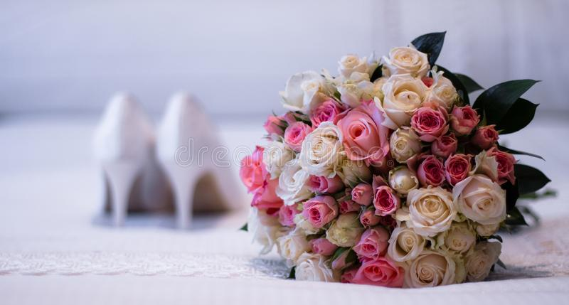 Flower bouquet and unfocused wedding shoes stock photography