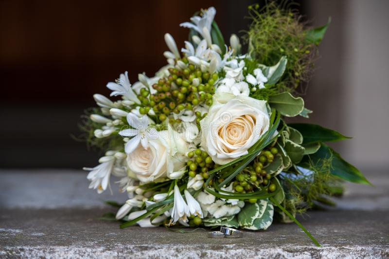 Flower bouquet and wedding rings on church stairs stock photo