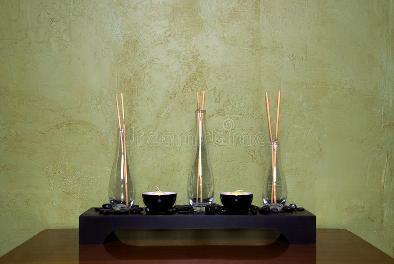 Flower and Candle Holder. With shiny black rocks surrounding them stock images