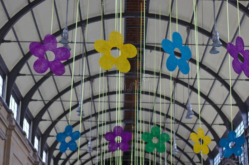 Flower celebration. Fake flowers hanging in the ceiling of a train station, bunch, colorful, blossom, arrangement, decor, decorative, transportation, festive royalty free stock photos