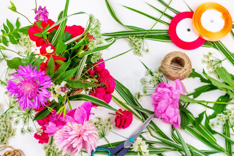 Flower composition with a bouquet of pink peony flowers, cornflowers and red roses and colored ribbons on a white background, top royalty free stock photo