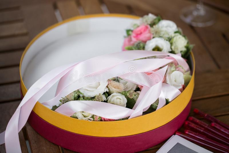 Flower composition, wedding bracelet of pink rose with ribbon and groom boutonniere on wooden table. Flower composition, wedding bouquet of pink rose with ribbon stock photo