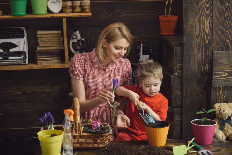 Flower concept. Mother and little son plant flower in pot. Flower shop. Every flower is a soul blossoming in nature.  stock photography