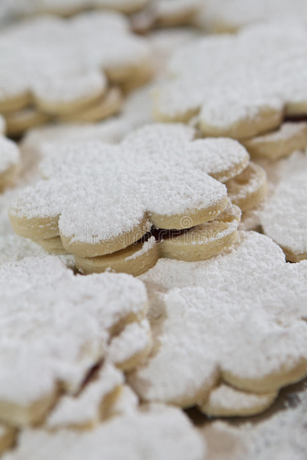 Flower Cookies. Close-up of flower-shaped cookies topped with powdered sugar. Center cookie is in focus stock photo