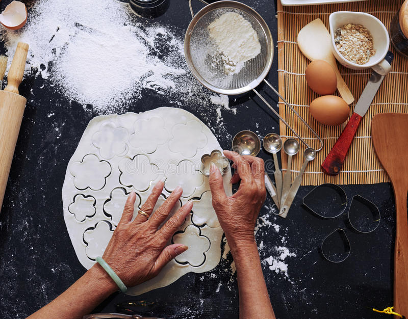 Flower cookies. Hands of housewife making flower cookies, view from above stock images