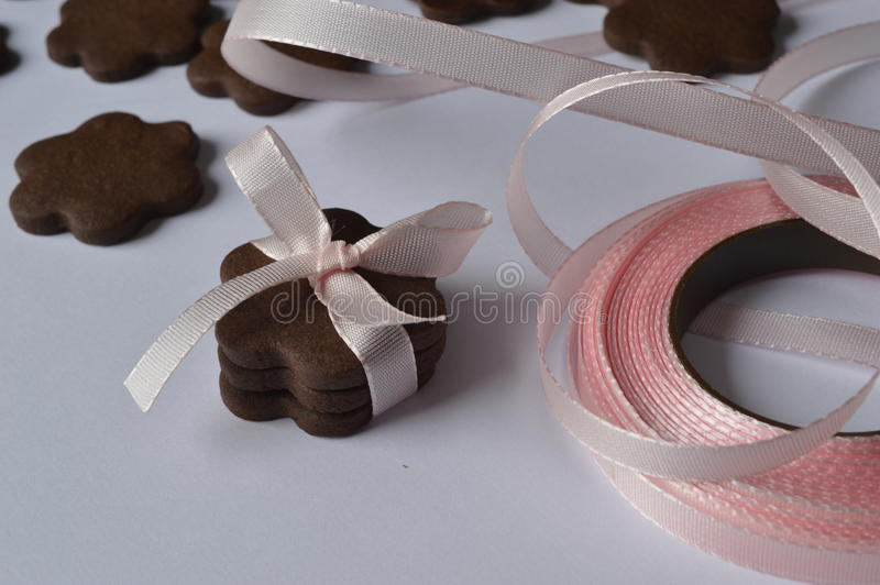 Flower cookies. Homemade dark chocolate flower shaped cookies with pale pink ribbon bow stock photo