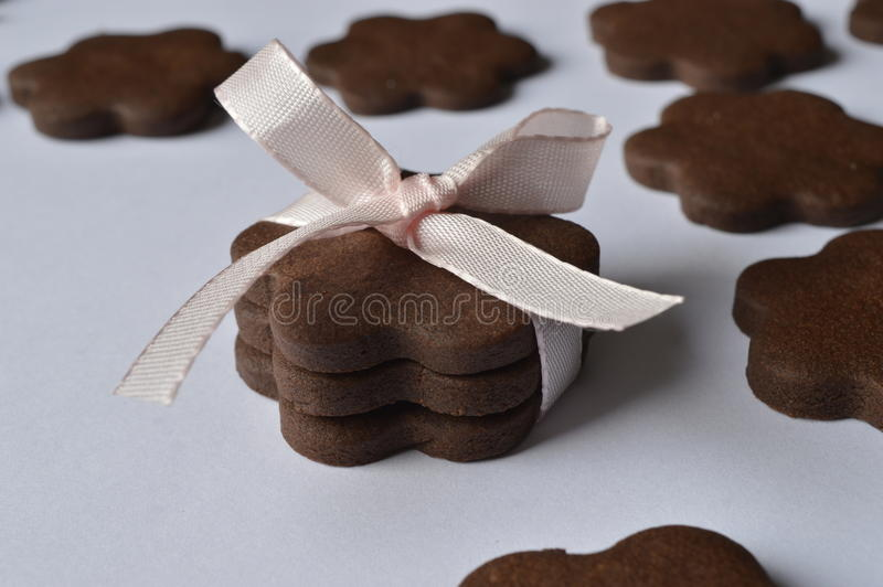 Flower cookies. Homemade dark chocolate flower shaped cookies with pale pink ribbon bow royalty free stock image