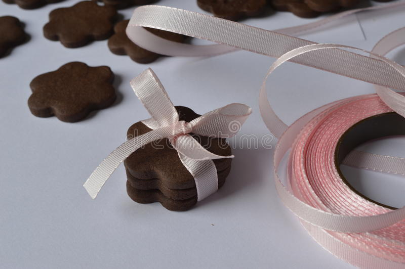 Flower cookies. Homemade dark chocolate flower shaped cookies with pale pink ribbon bow royalty free stock images