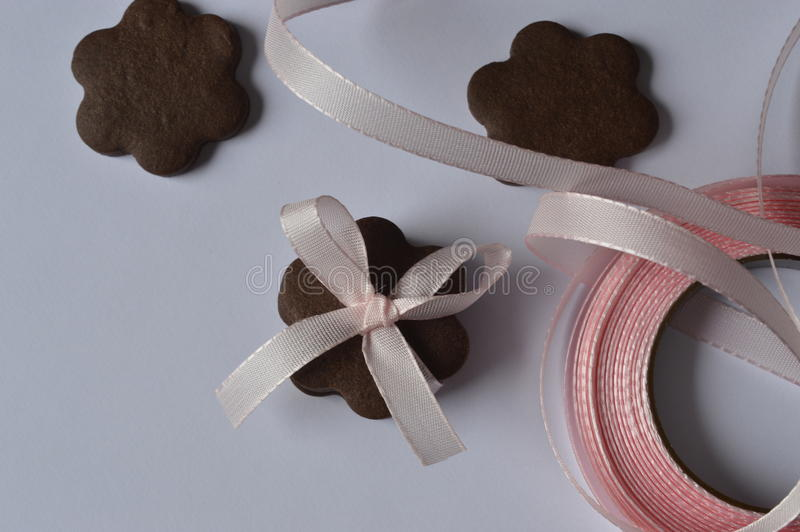 Flower cookies. Homemade dark chocolate flower shaped cookies with pale pink ribbon bow stock photos
