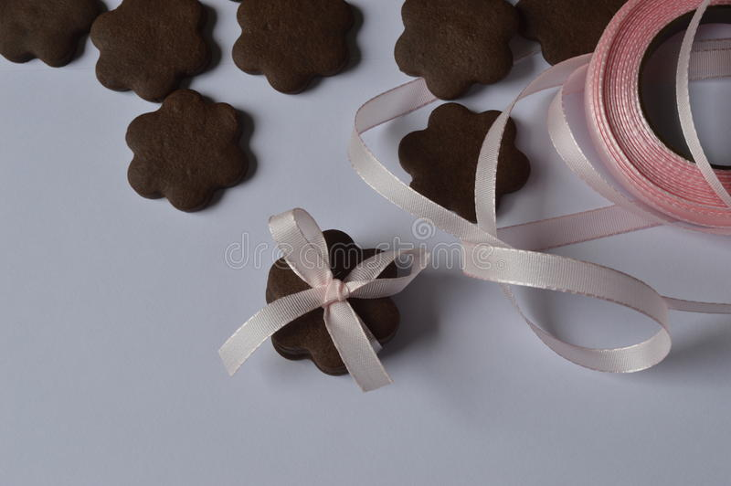 Flower cookies. Homemade dark chocolate flower shaped cookies with pale pink ribbon bow stock images