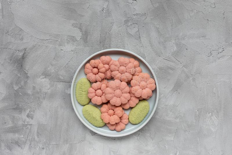 Flower cookies on a plate on a gray background . Spring holidays cooking concept. Top view, flat lay, copy space stock images